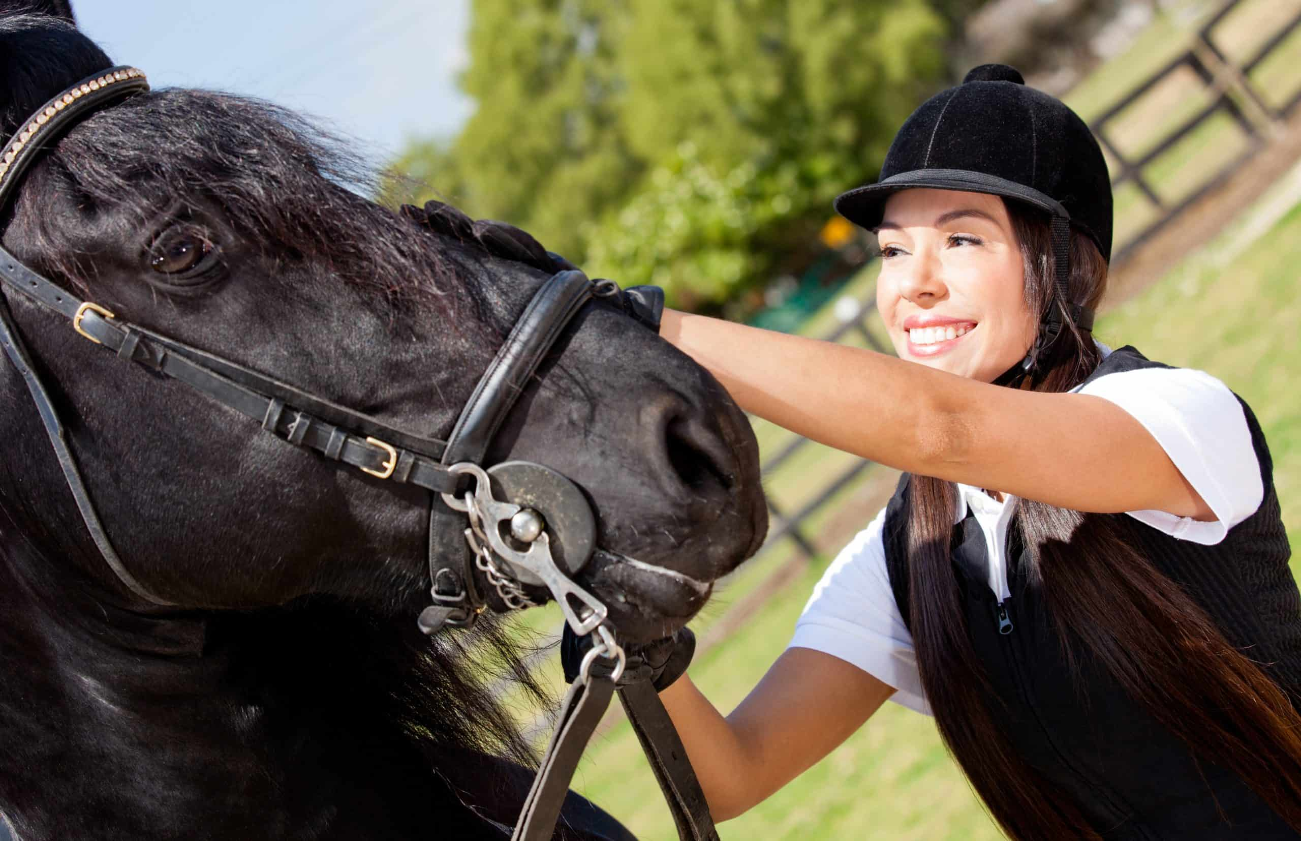 Portrait of a happy female jockey stroking a horse