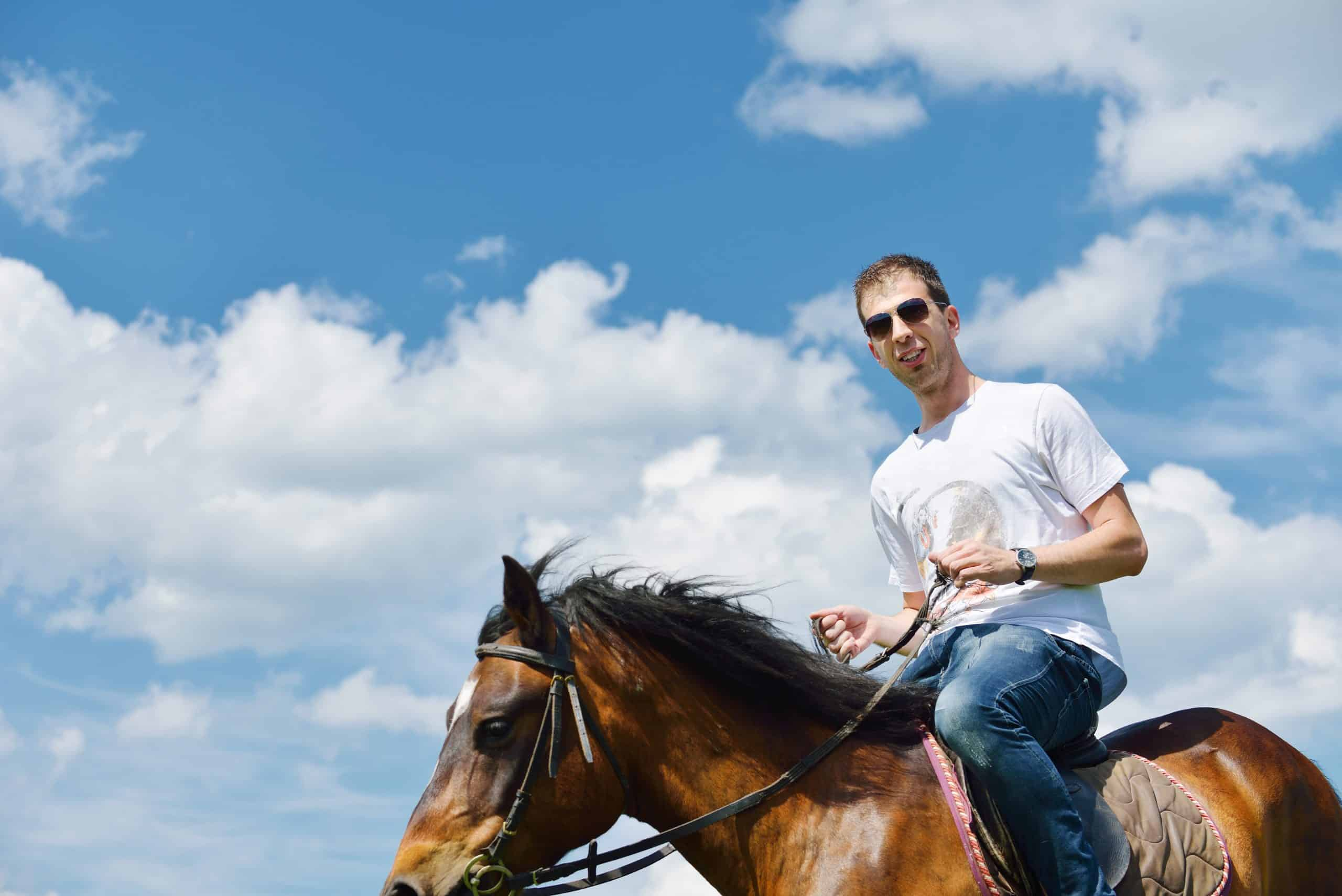young man on horseback farm animal with blue sky in background