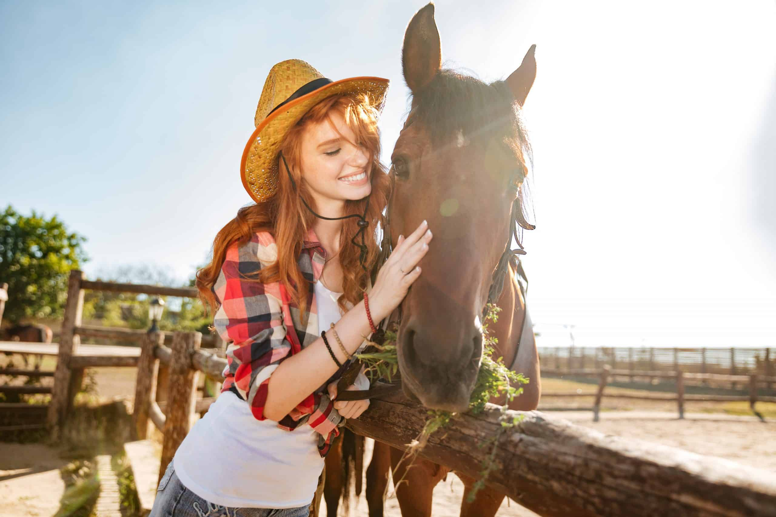 Smiling cute young woman cowgirl taking care and hugging her horse