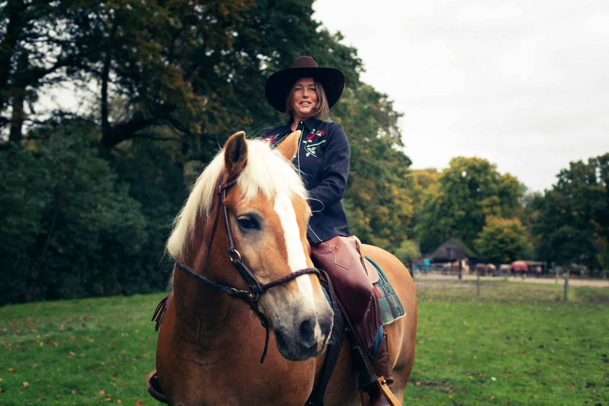 Smiling western style woman horse riding in countryside.