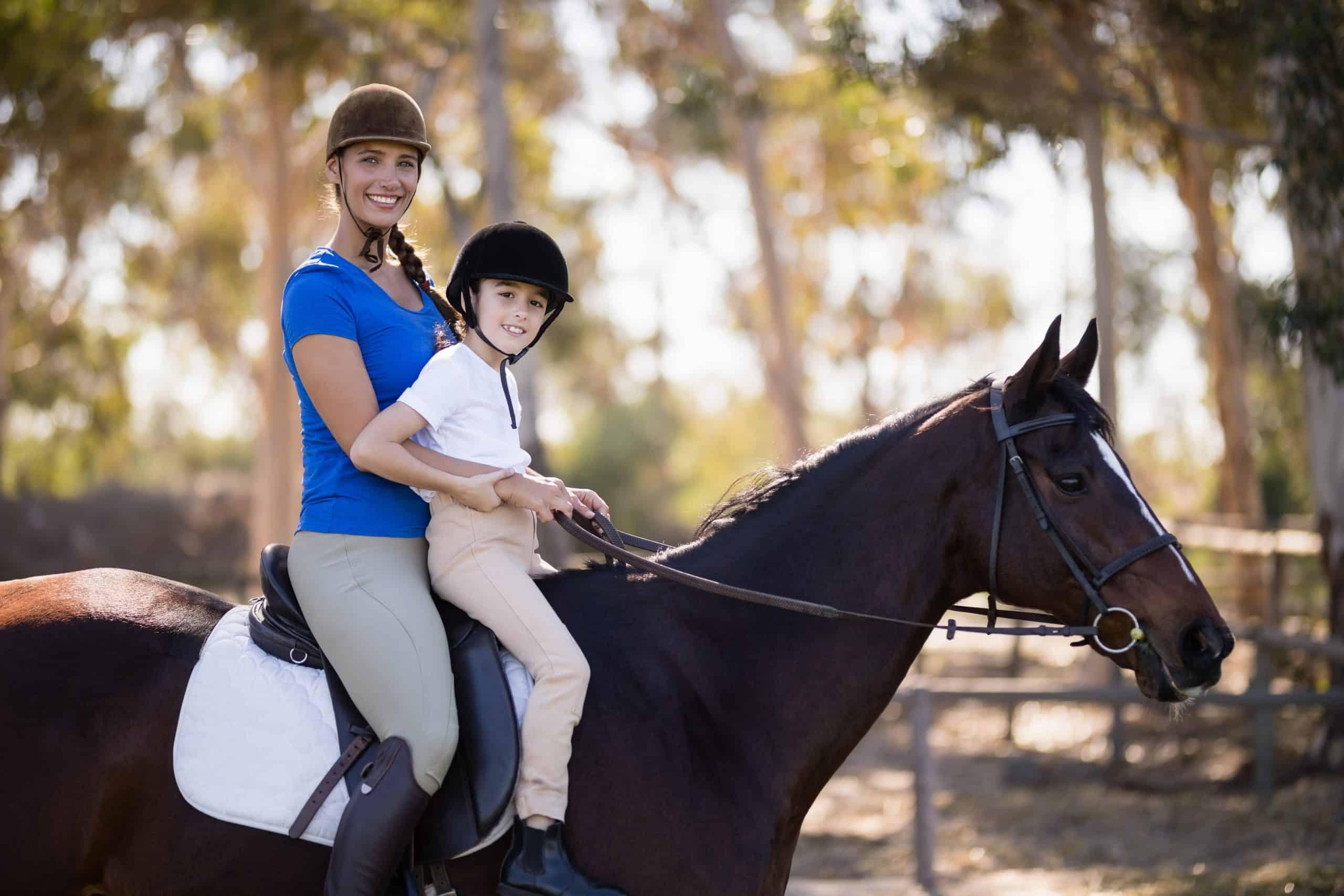 Portrait of Female jockey and girl sitting horseback riding at paddock