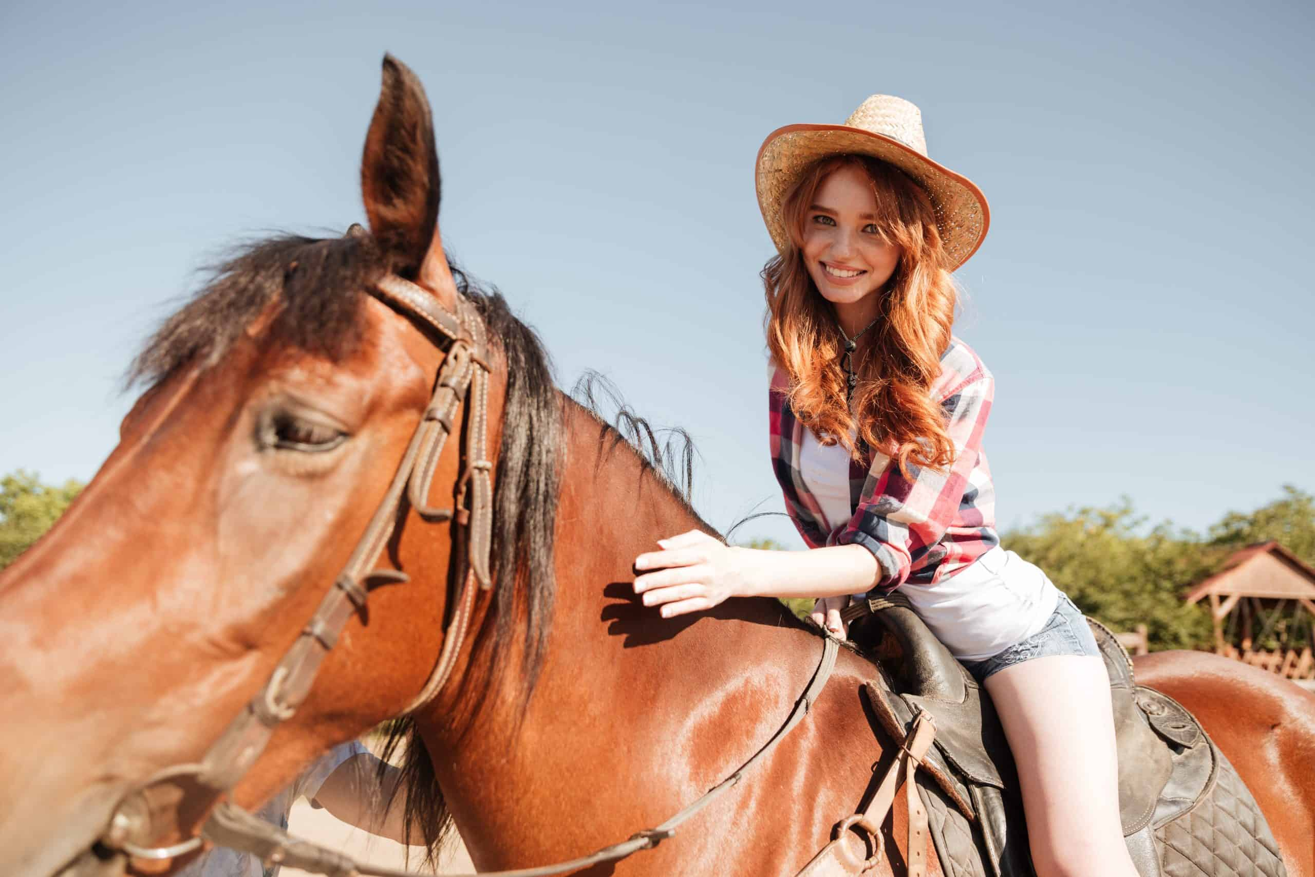 Happy young person cowgirl riding horse on ranch