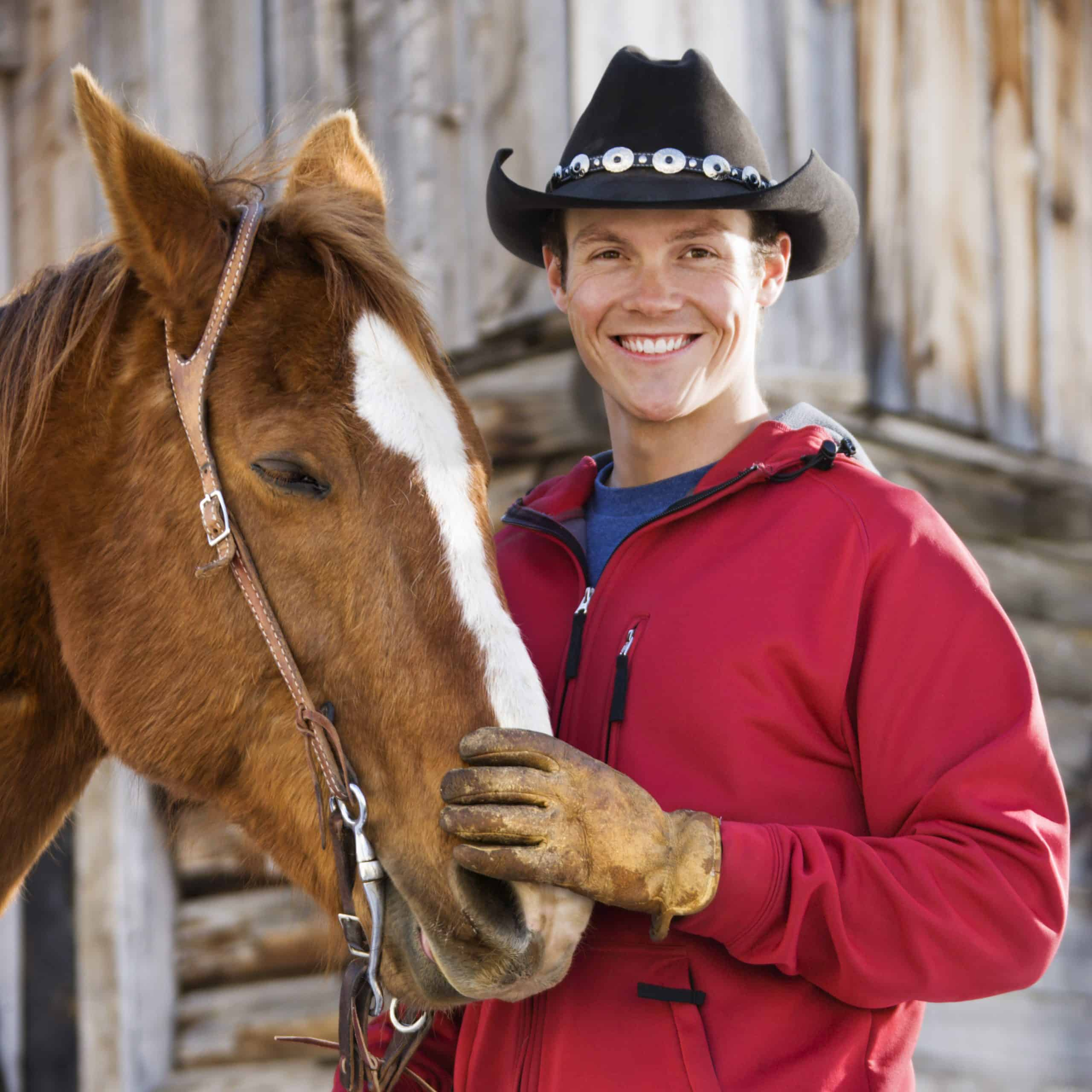 Young man in cowboy hat petting his horse.