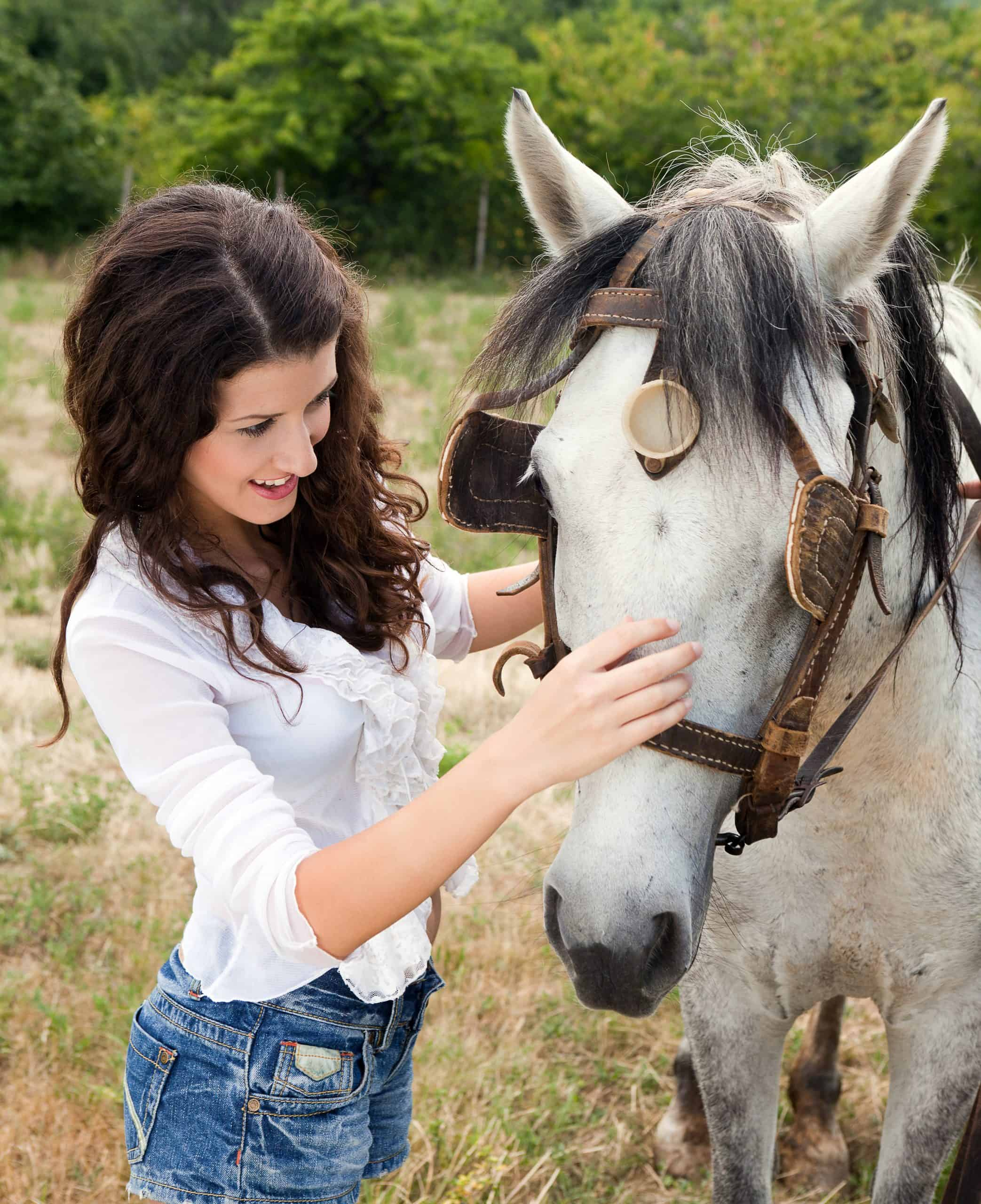 Smiling woman meeting a farm horse in a meadow