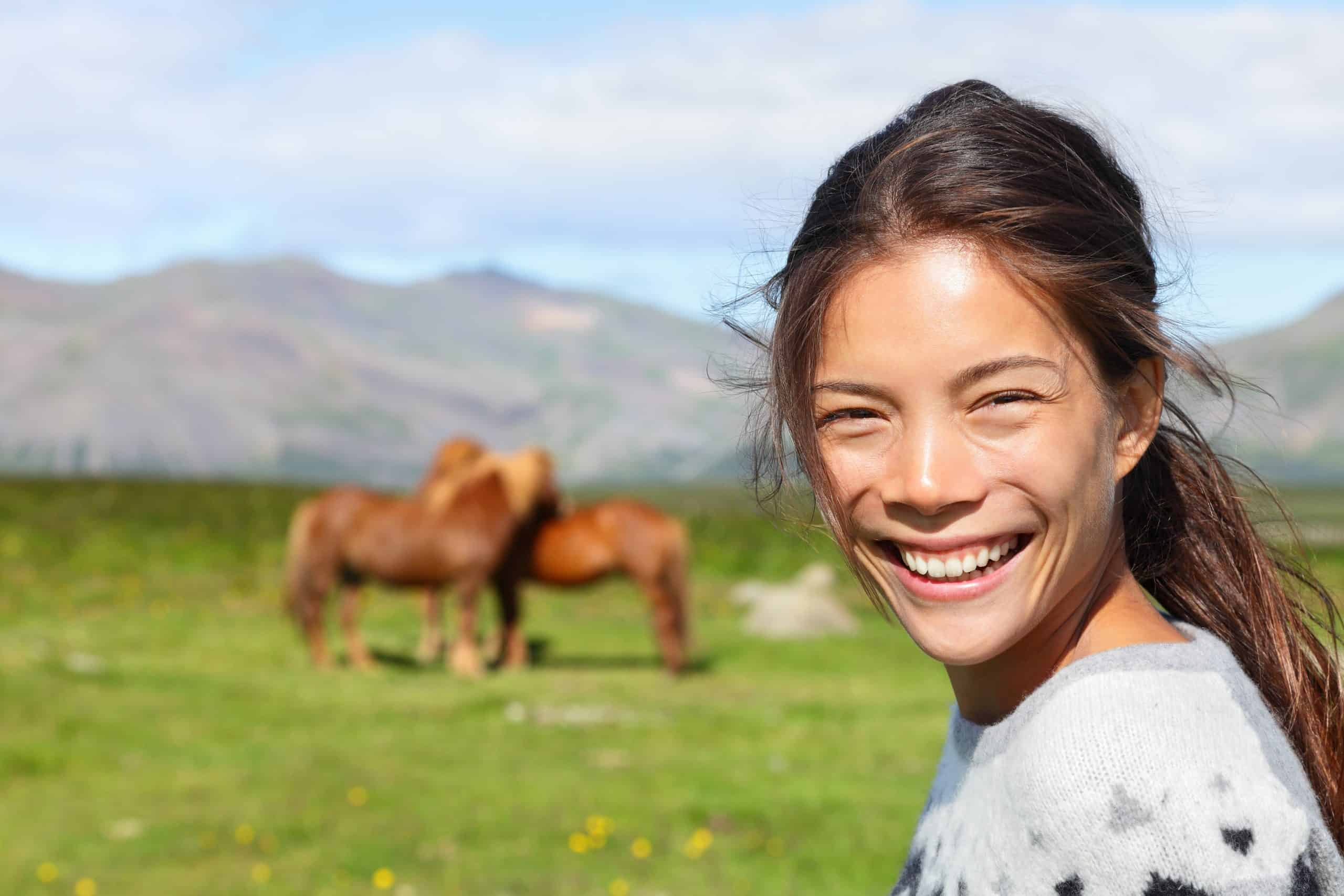 Woman on Iceland smiling with Icelandic horses. Portrait of happy multicultural girl wearing Icelandic sweater standing outdoors in nature field in front of horse.