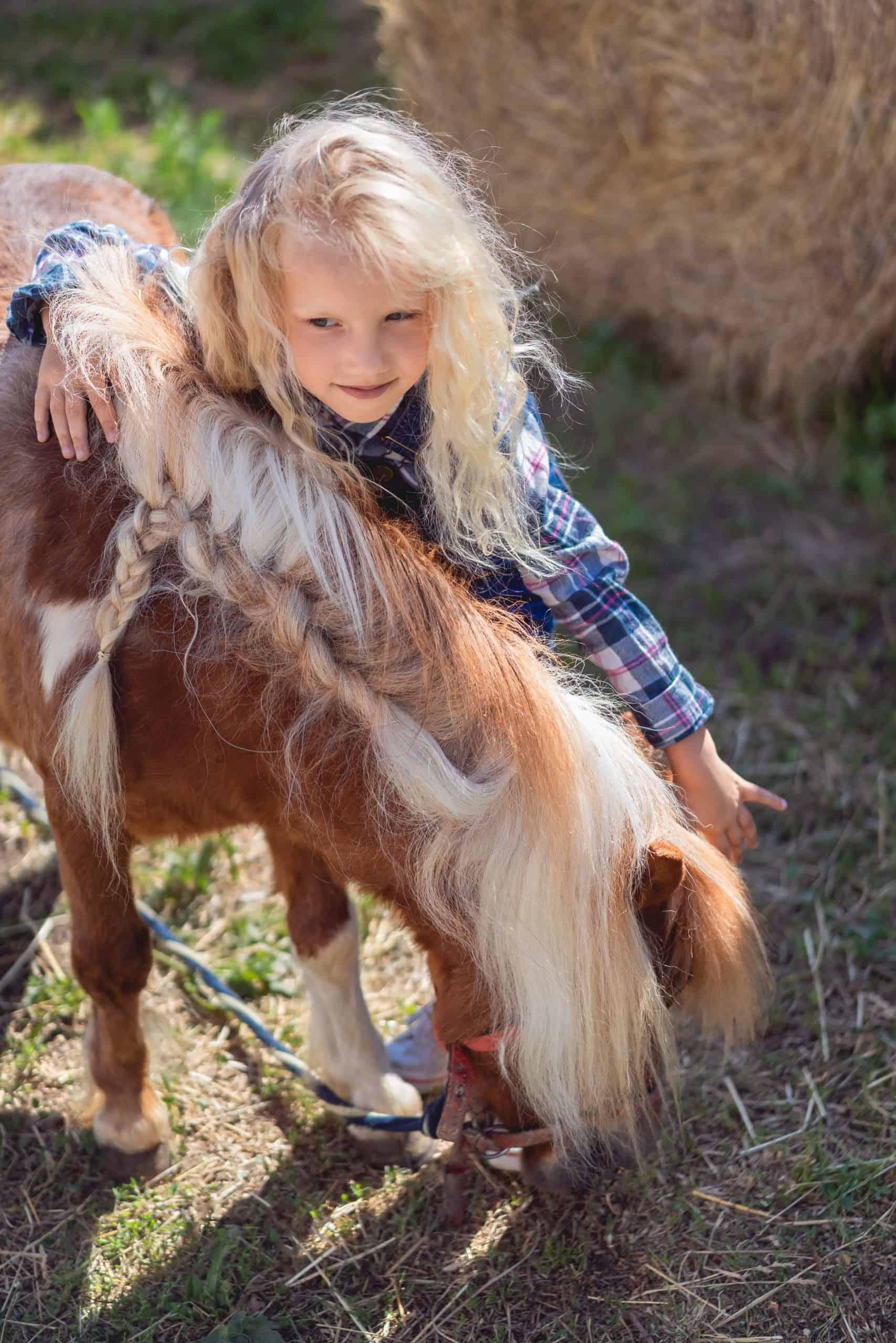 preteen child hugging cute equine at farm