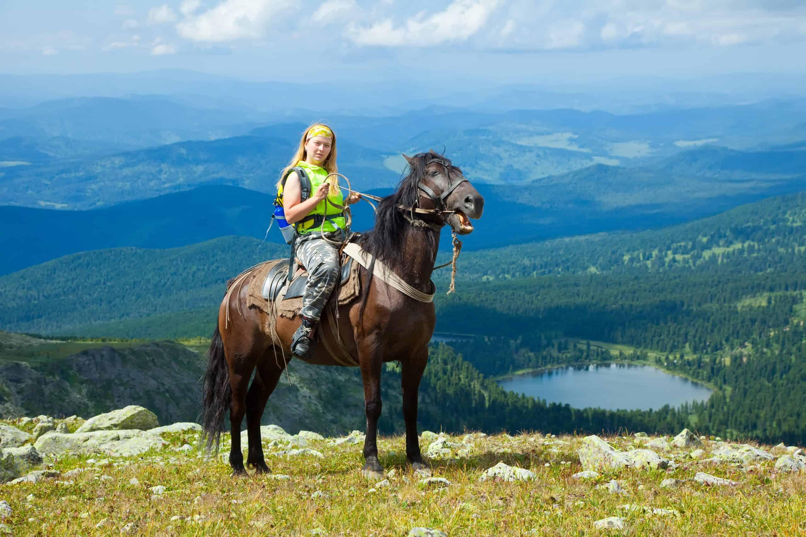 Female rider on horseback at mountains peak. Karakol lakes, Altai
