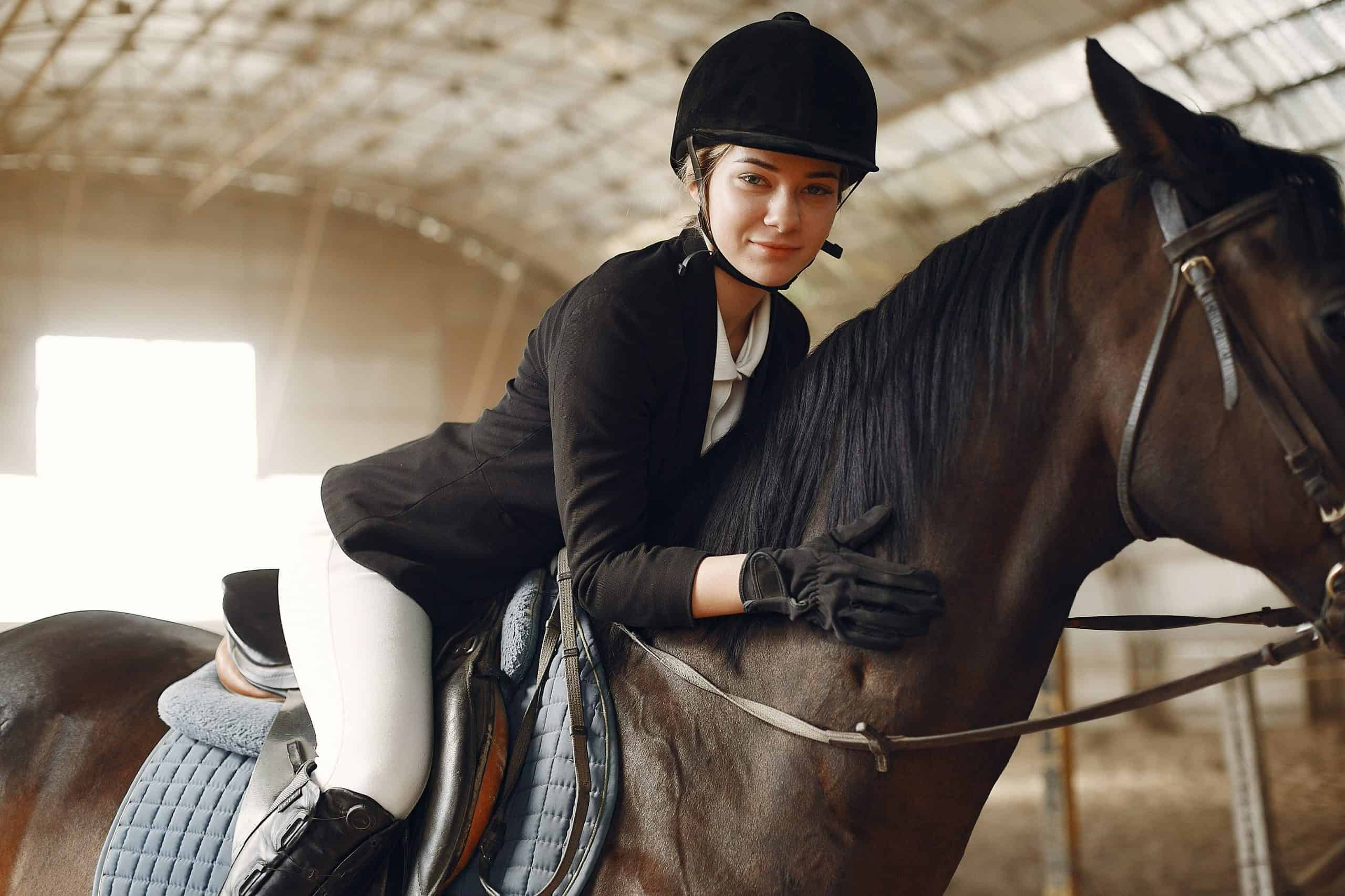 Woman on a horseback. Rider in a black uniform