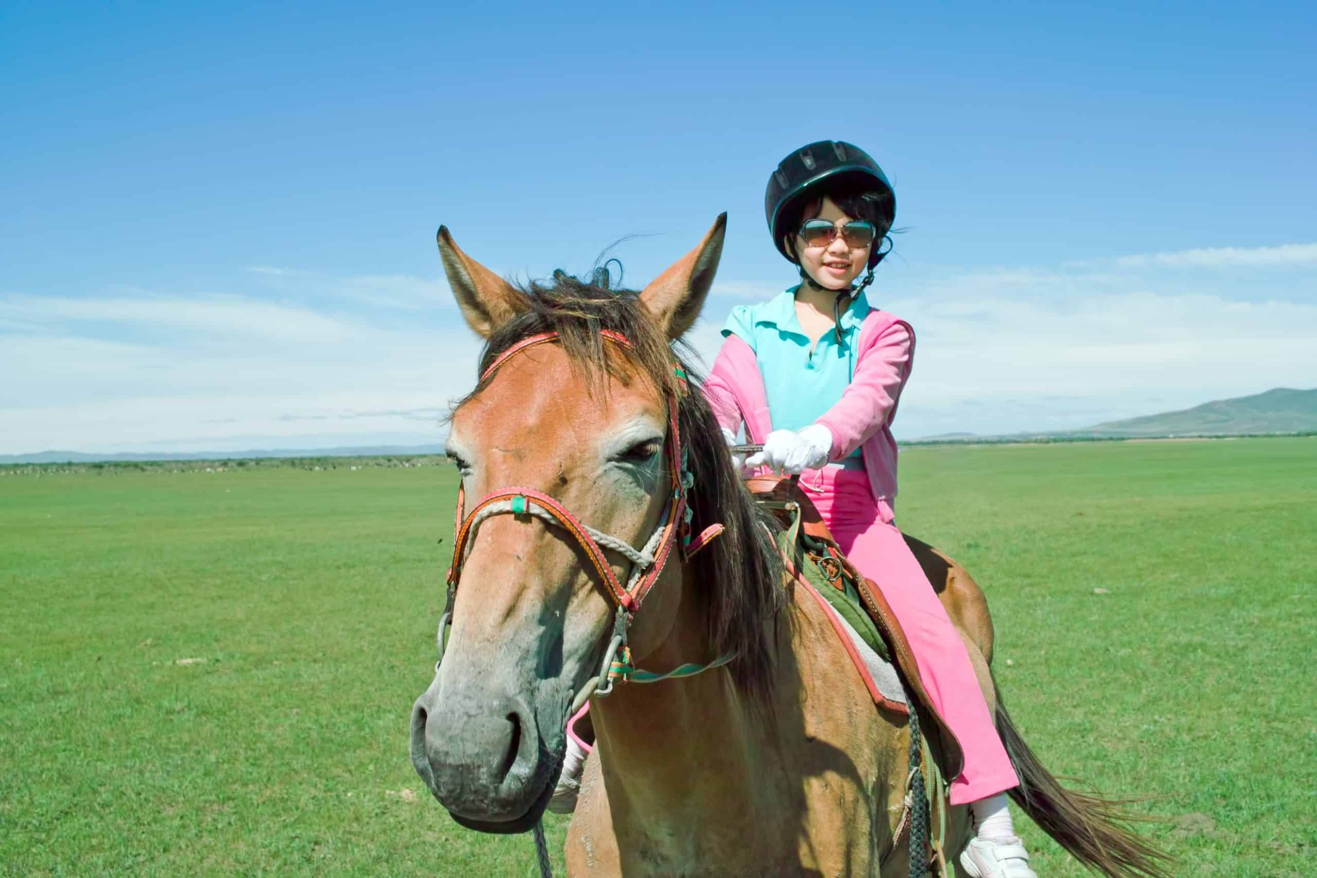 An Asian kid riding horse in the grassland