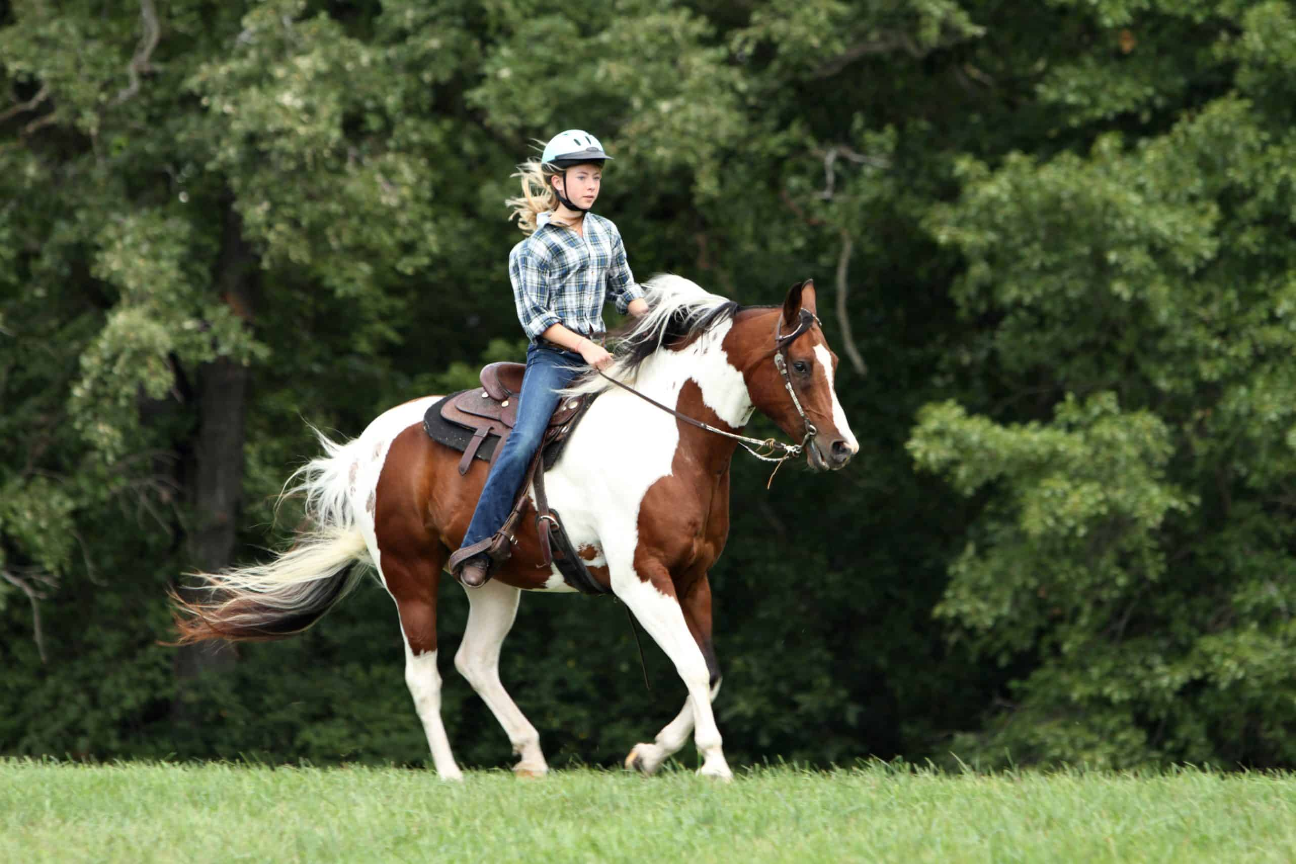 Teenage girl riding a running horse