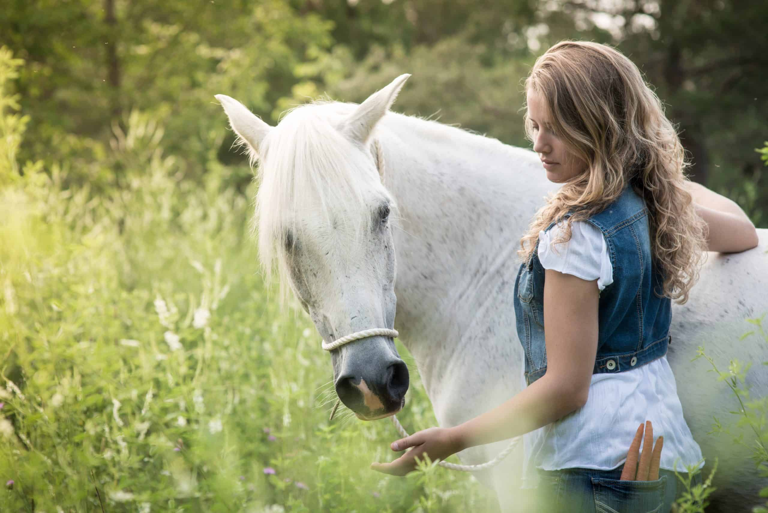 Beautiful Blond Girl Feeding carrots to her white horse