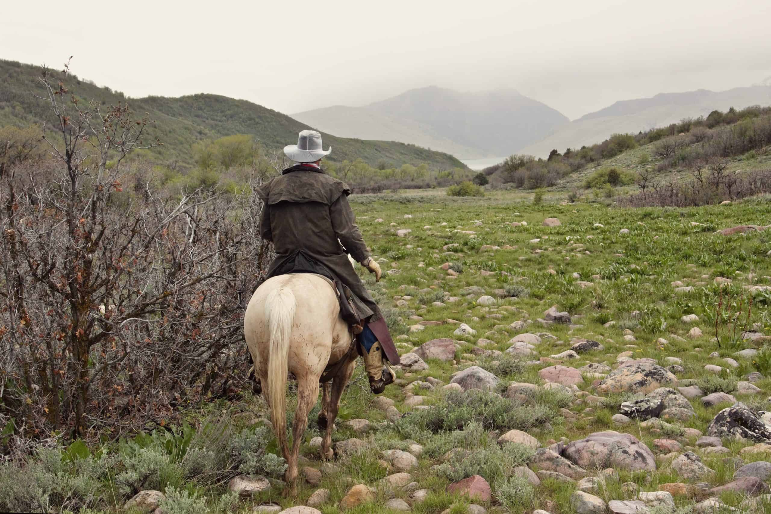 cowboy riding white horse in stormy weather