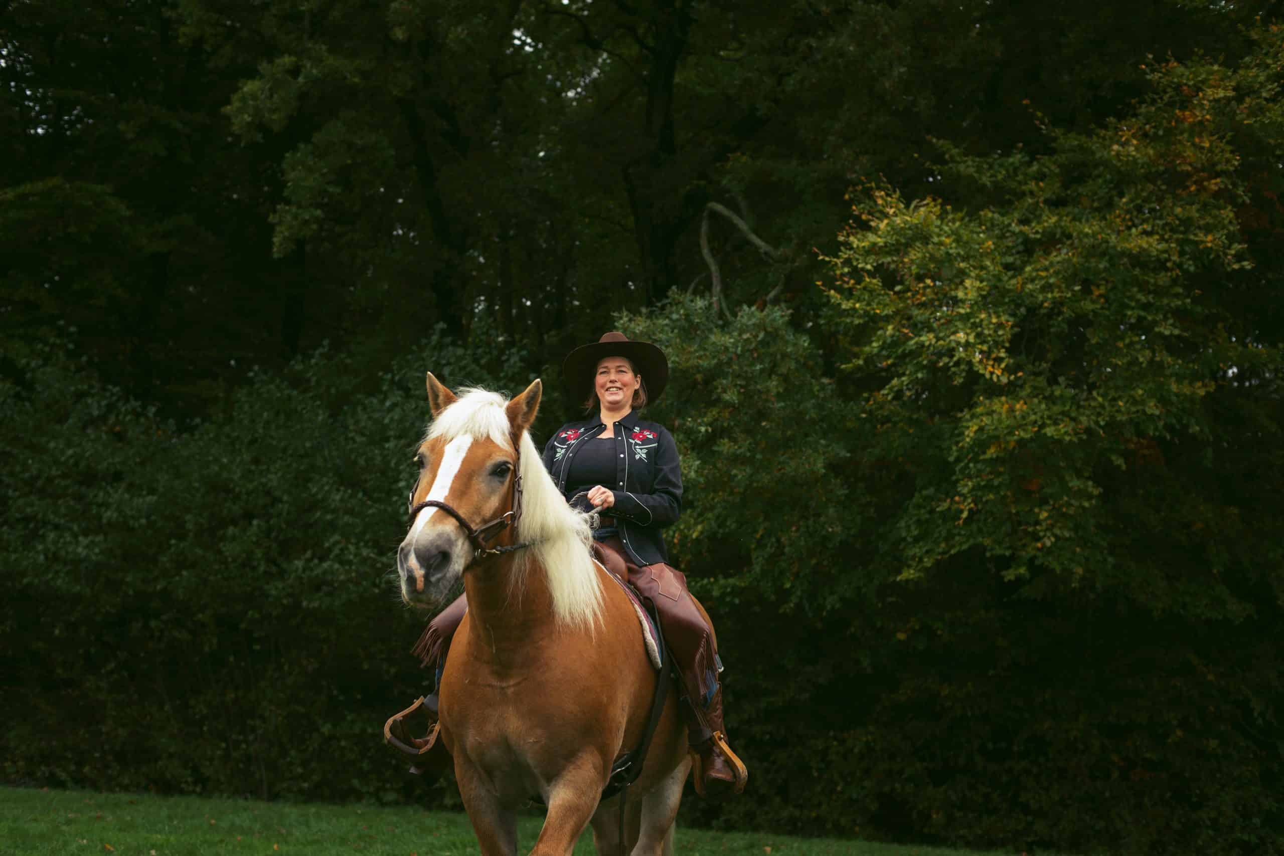 Smiling woman with hat horse riding in forest.