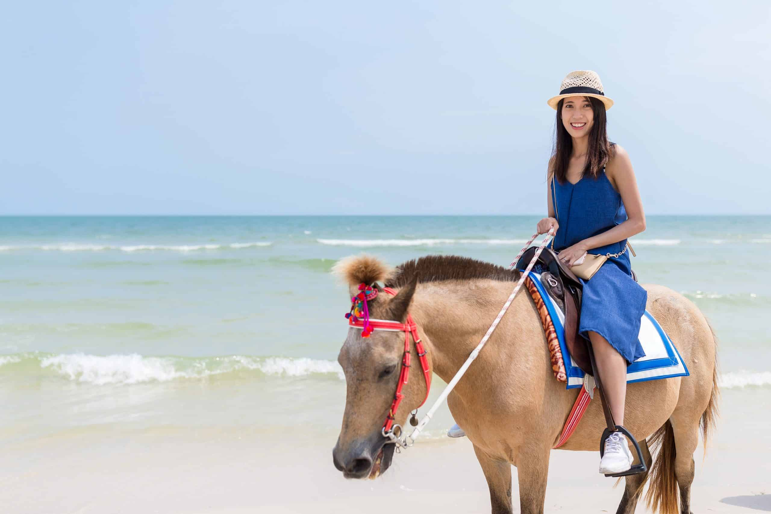 Woman riding horse in the sand beach