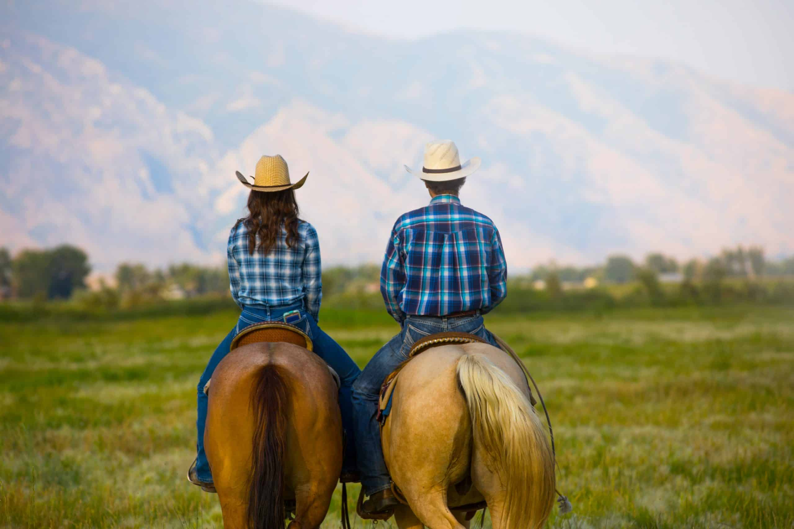 A cowboy and cowgirl horseback looking over the prairie in the Western USA.