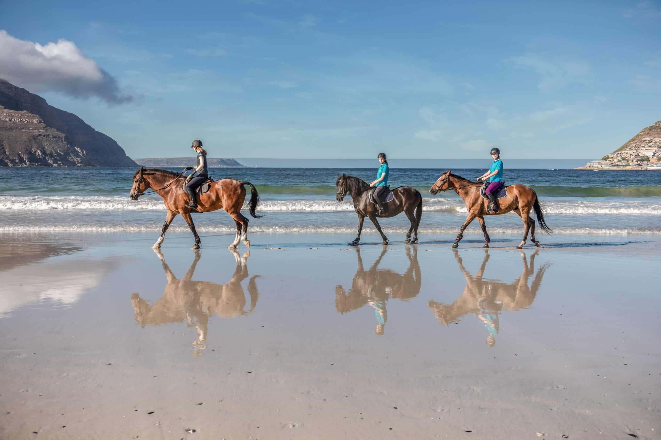Three teenage girls on horseback walking in the water at low tide on the beach with a beautiful mountain in the background and reflections of themselves in the water on the shore