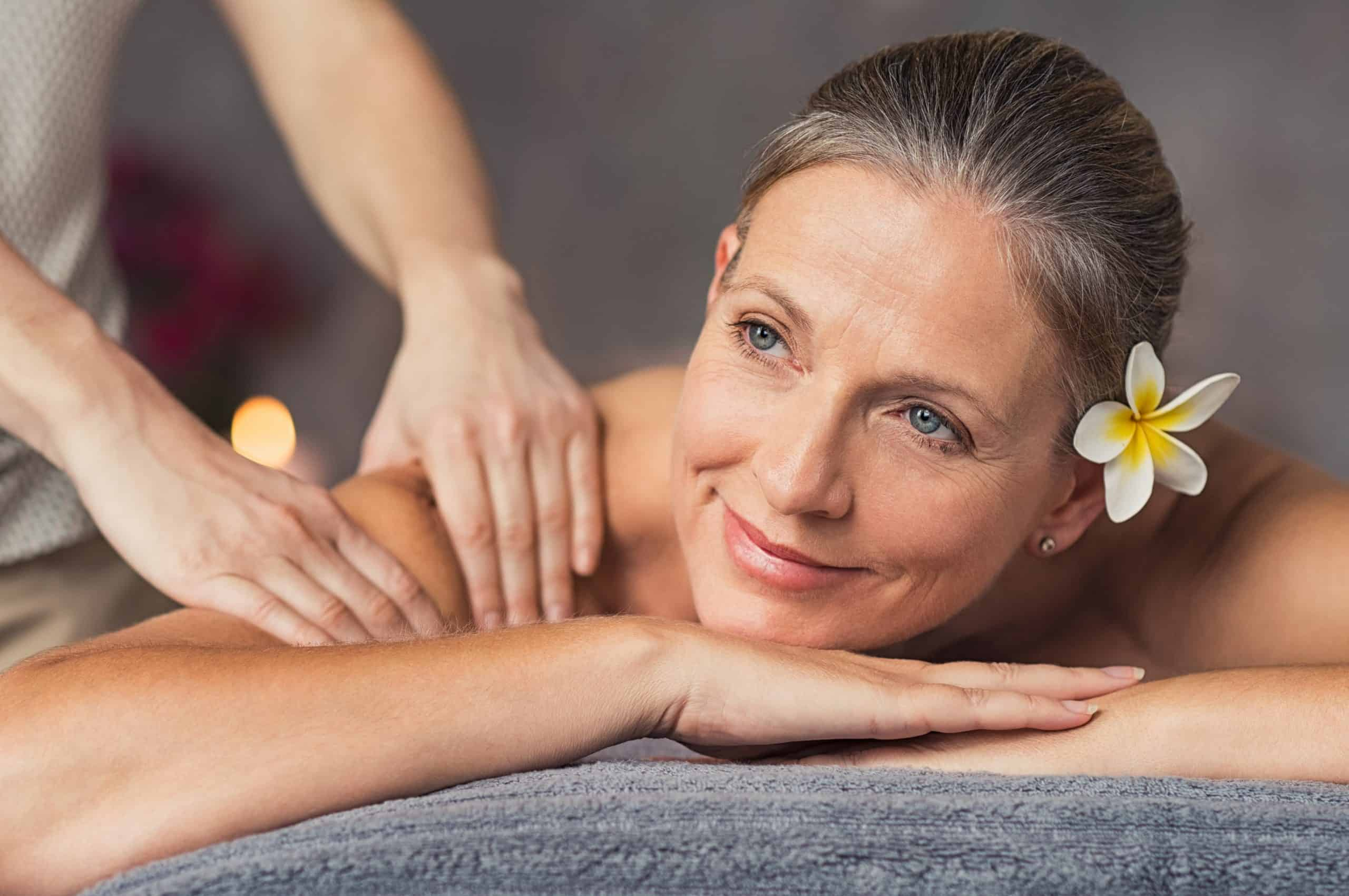 "Senior woman in spa salon getting massage. Closeup of a beautiful woman during spa treatment. Beautiful mature woman receiving massage of shoulder at beauty salon.""r"