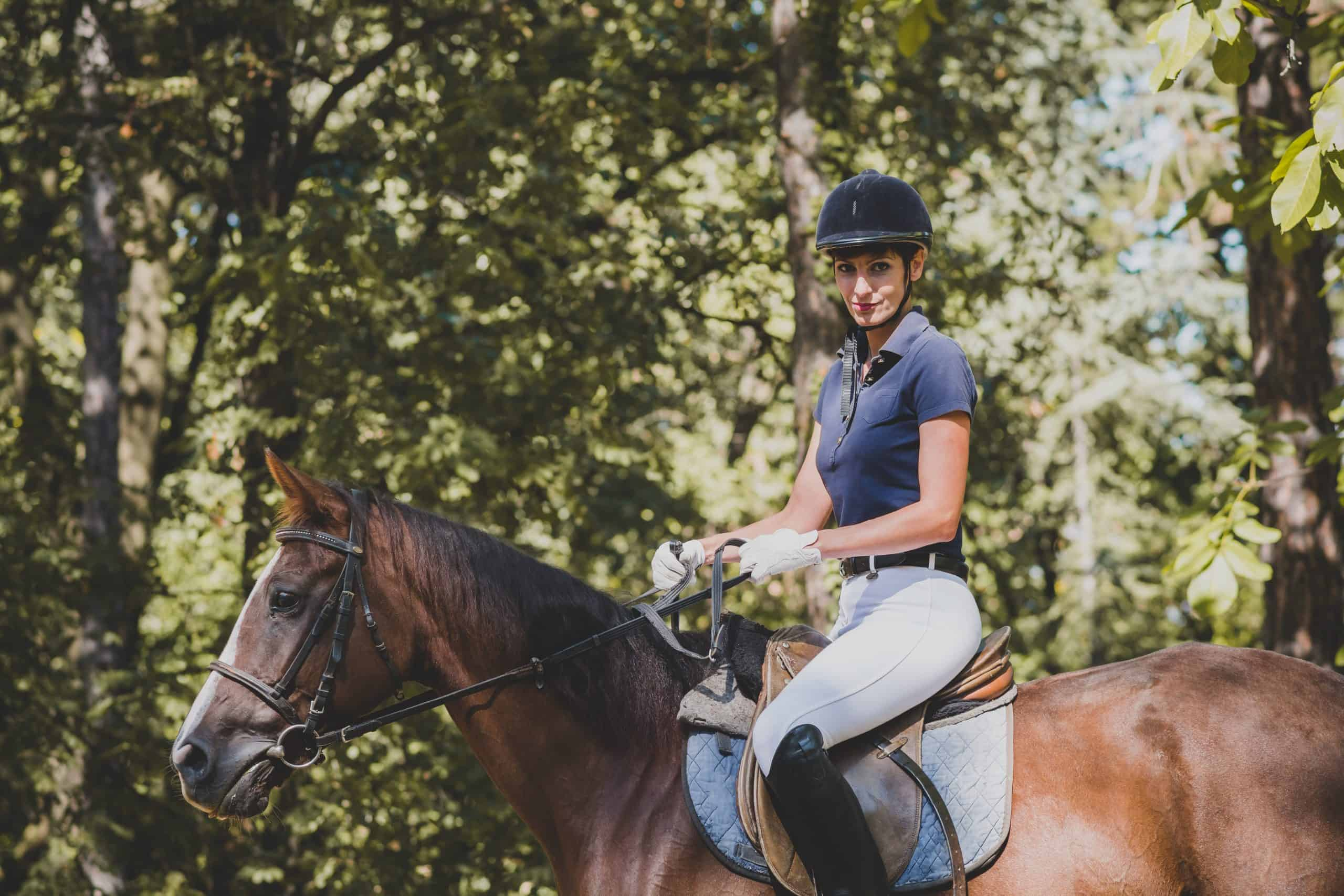 Young smiling woman riding horse in nature