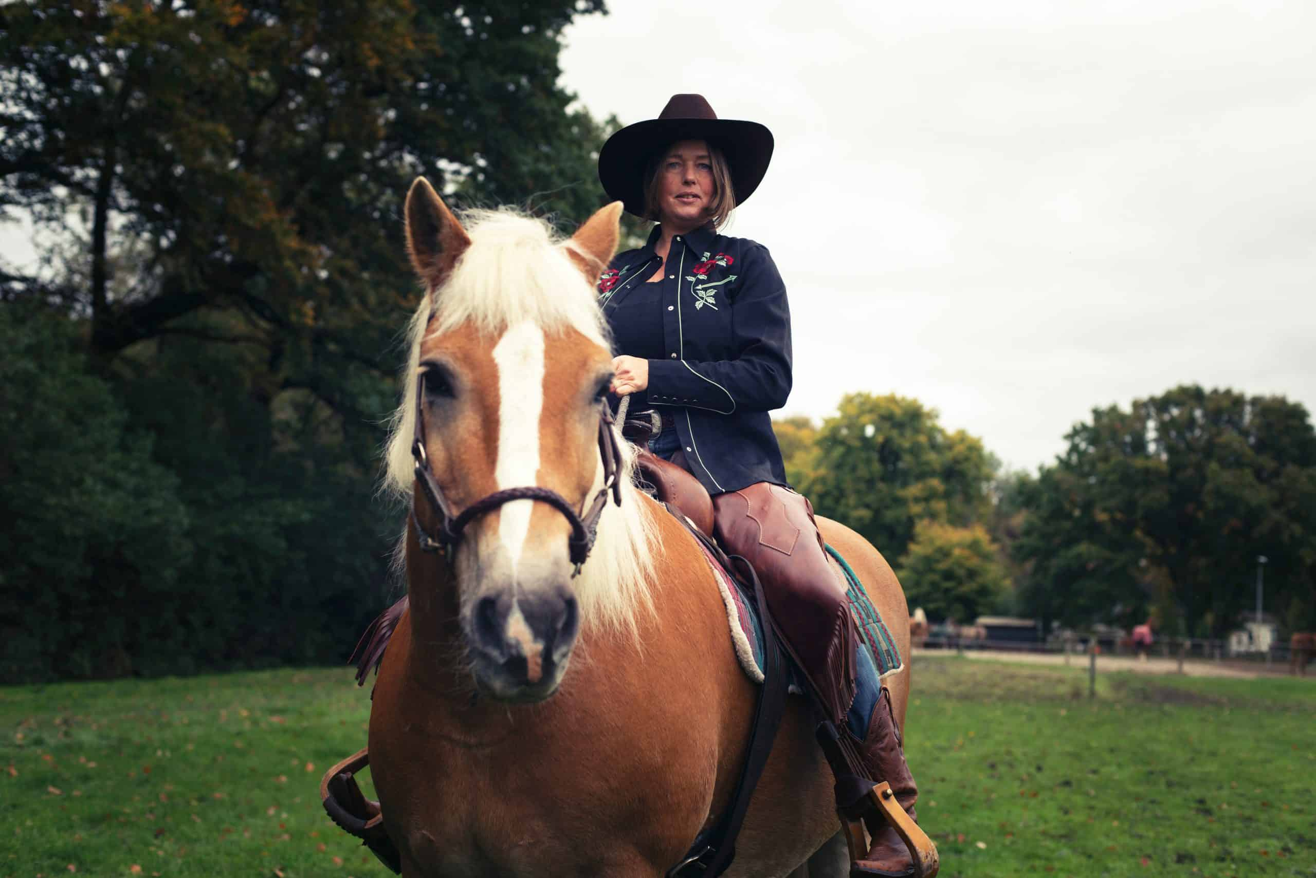 horses mental health benefits Smiling western style woman horse riding in countryside.