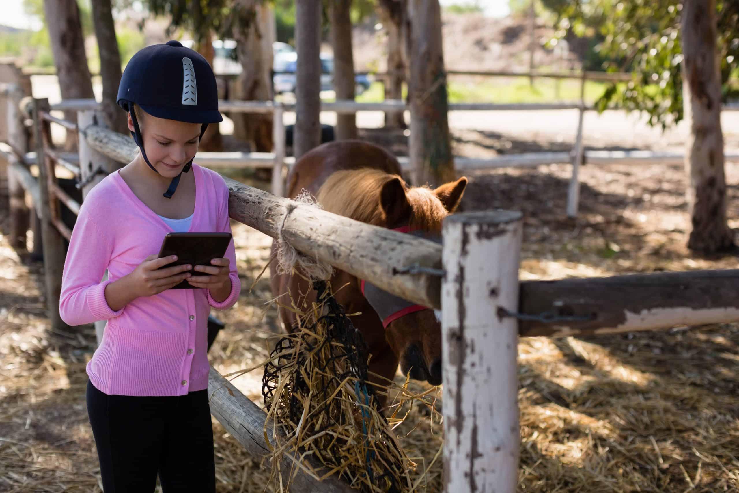 Girl using digital tablet at the ranch