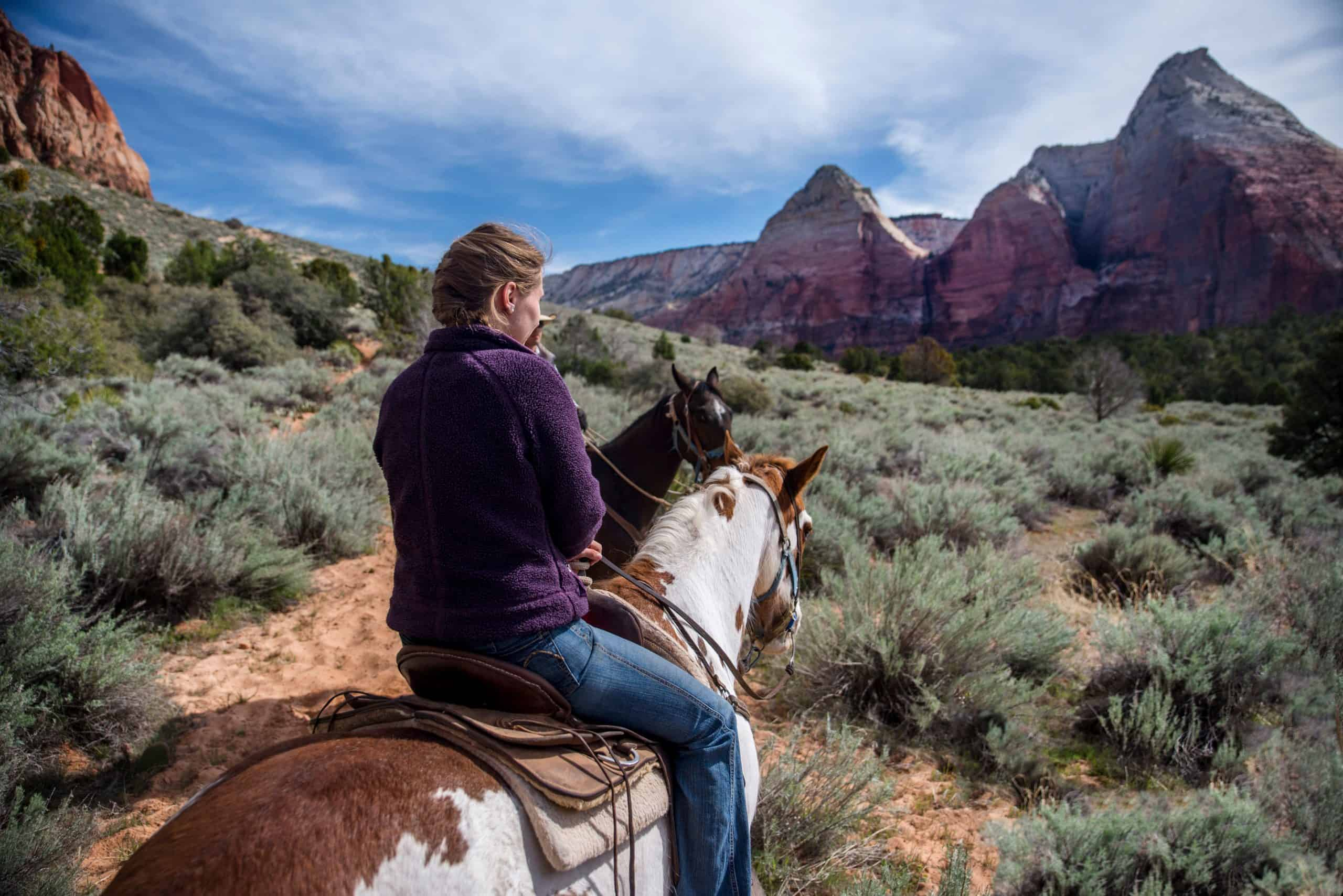 A woman rides on a painted horse through Zion Canyon in Zion National Park, Utah.