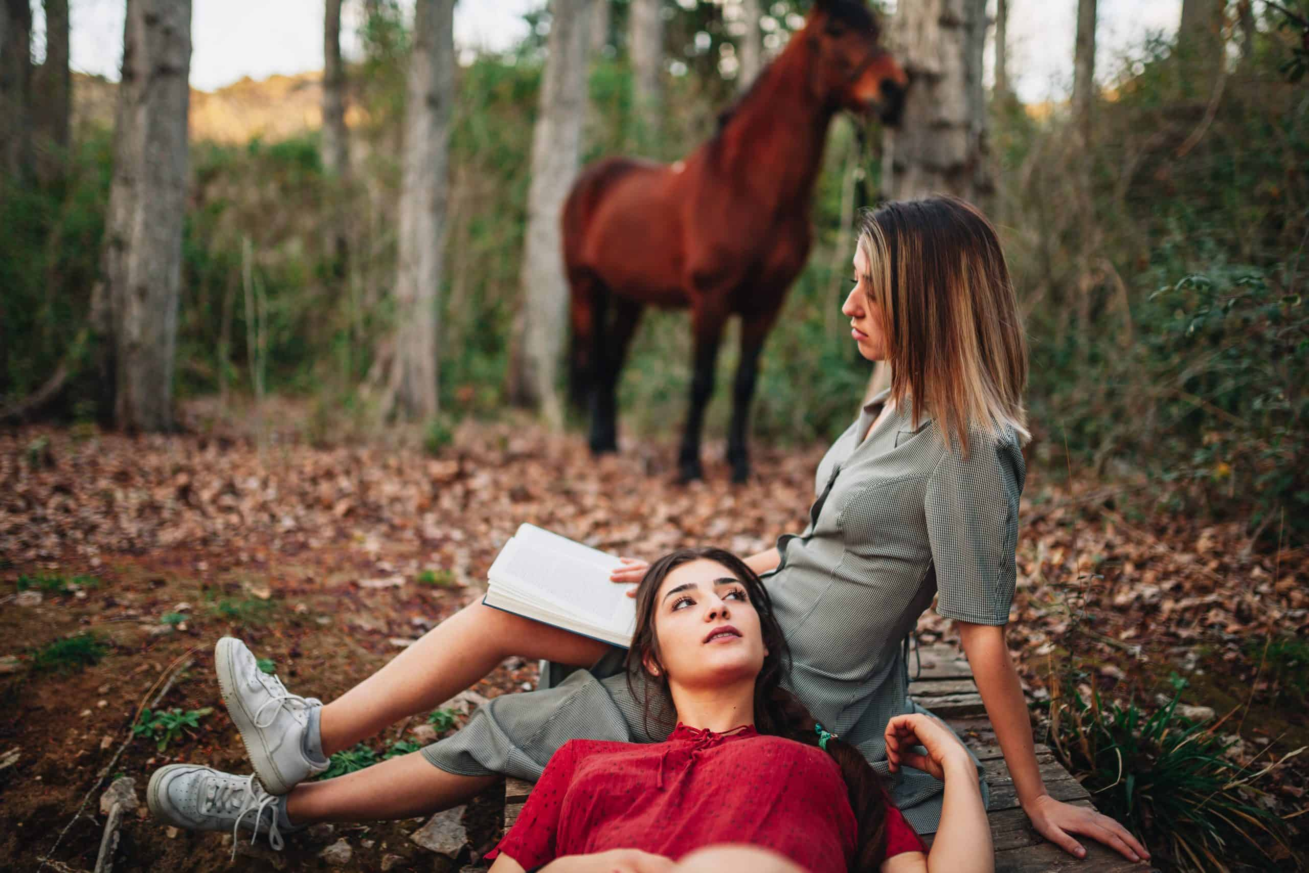 Young couple of women wearing dresses reading a book and taking photos with old camera in the forest with their horse.