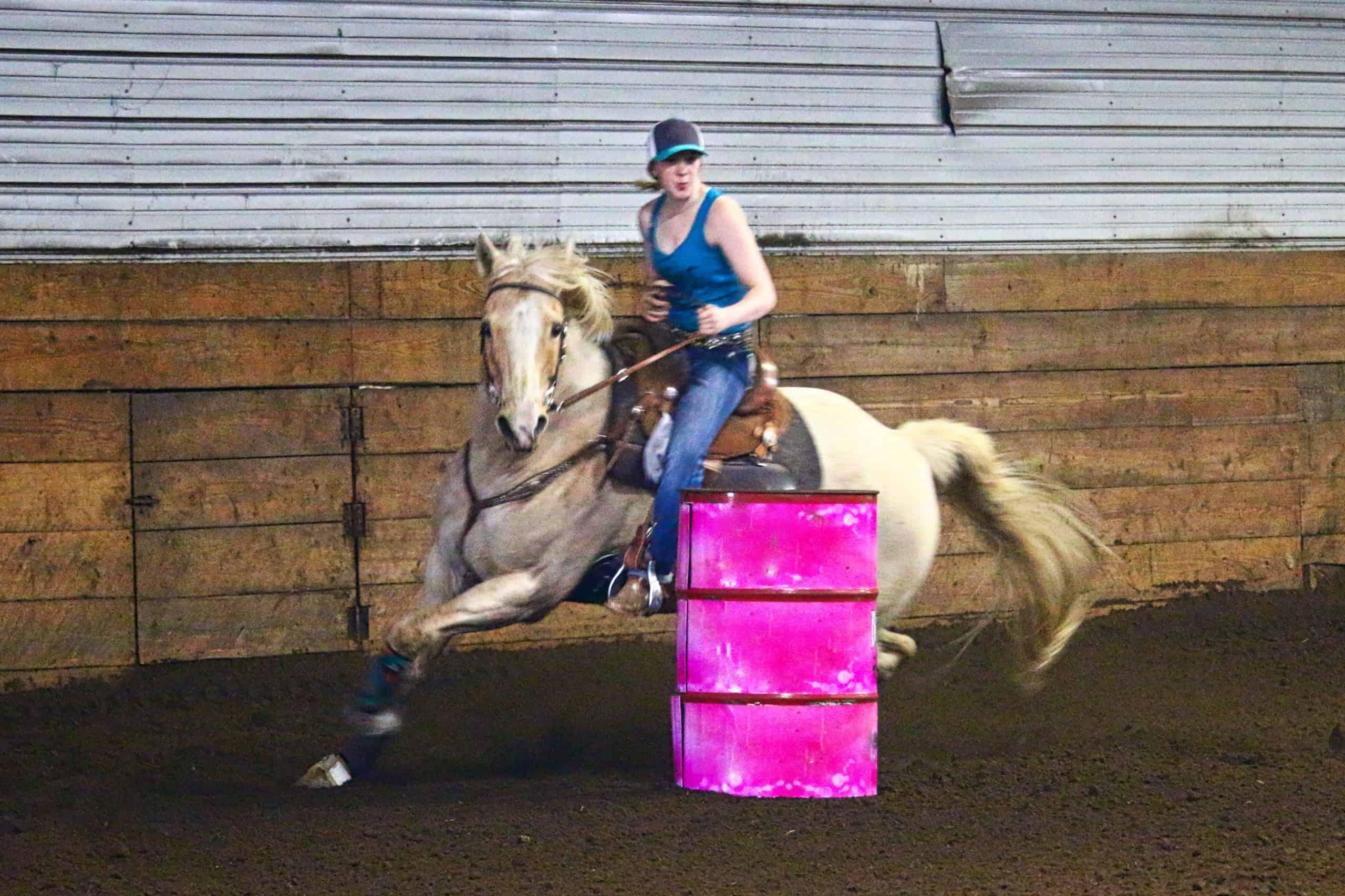 Barrel racing indoors on palomino horse around pink barrel