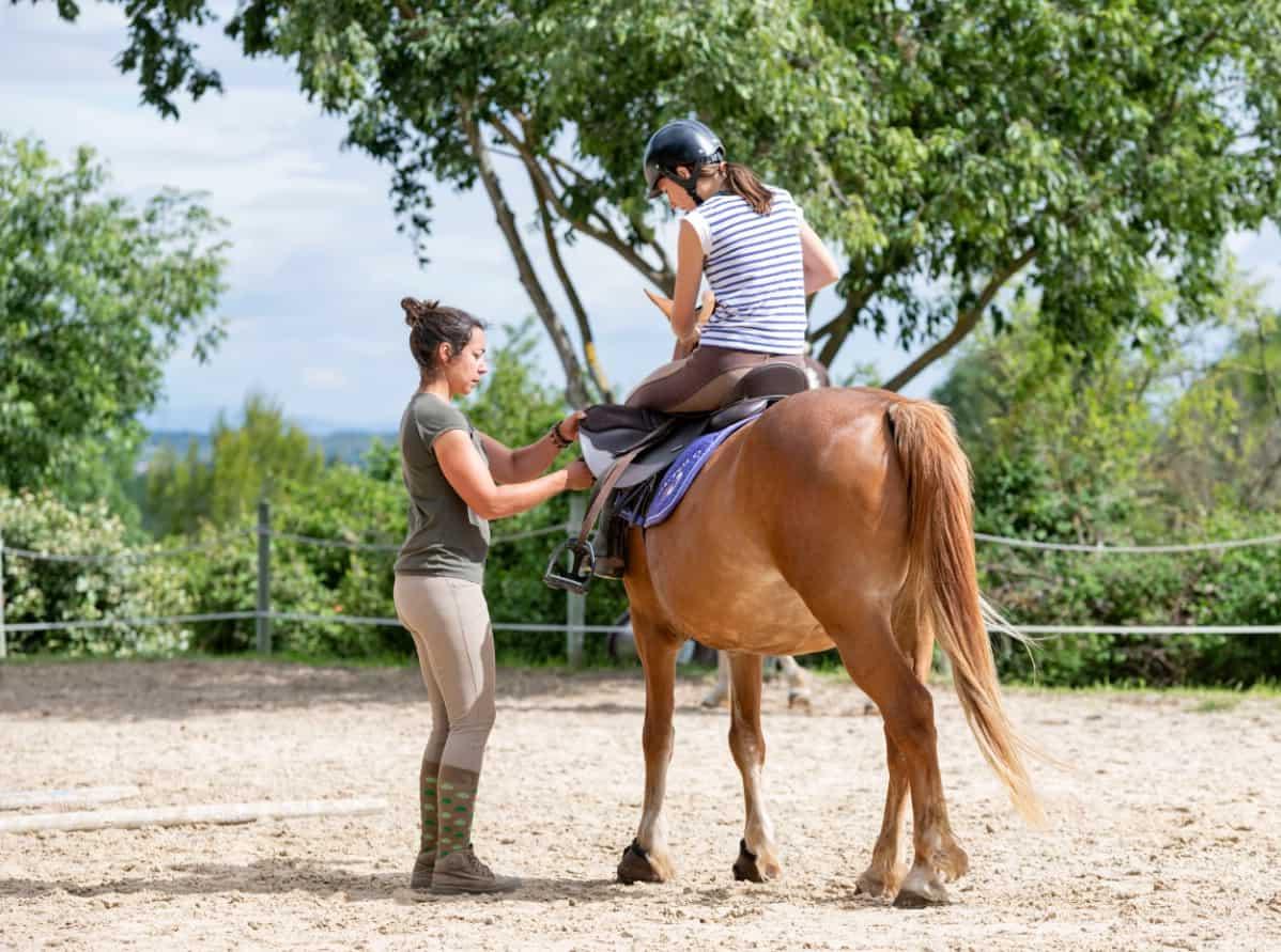 Horse instructor teaching children.
