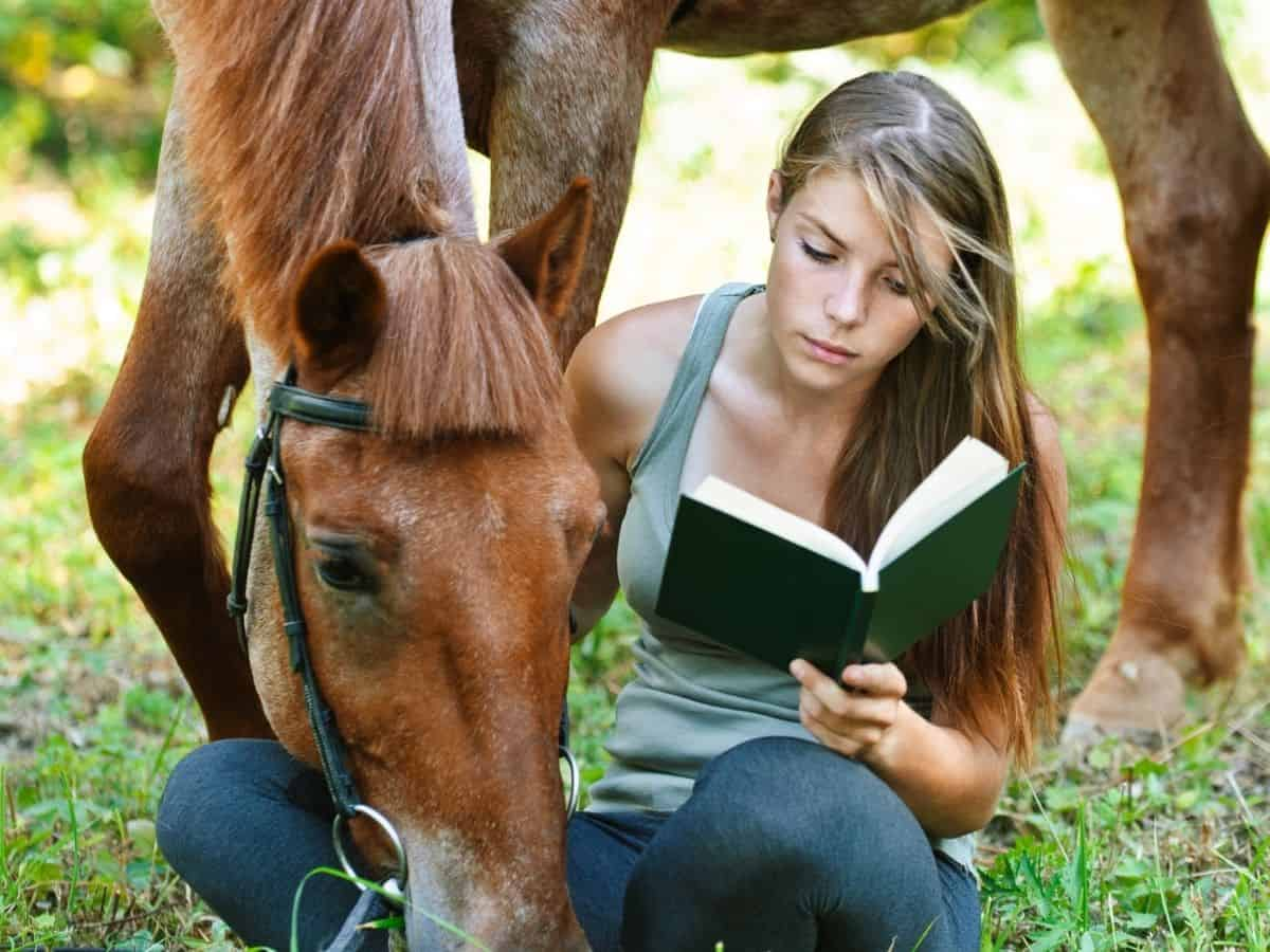 Girl reading book by horse