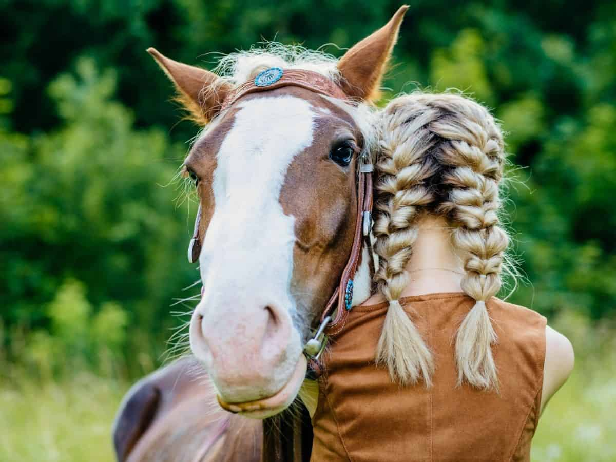 Blonde in braids hugging horse