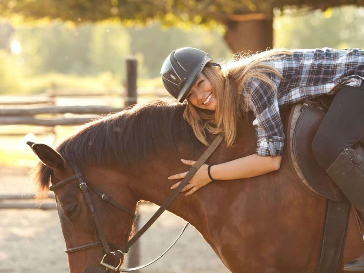 Girl with riding hat laying on horse to hug