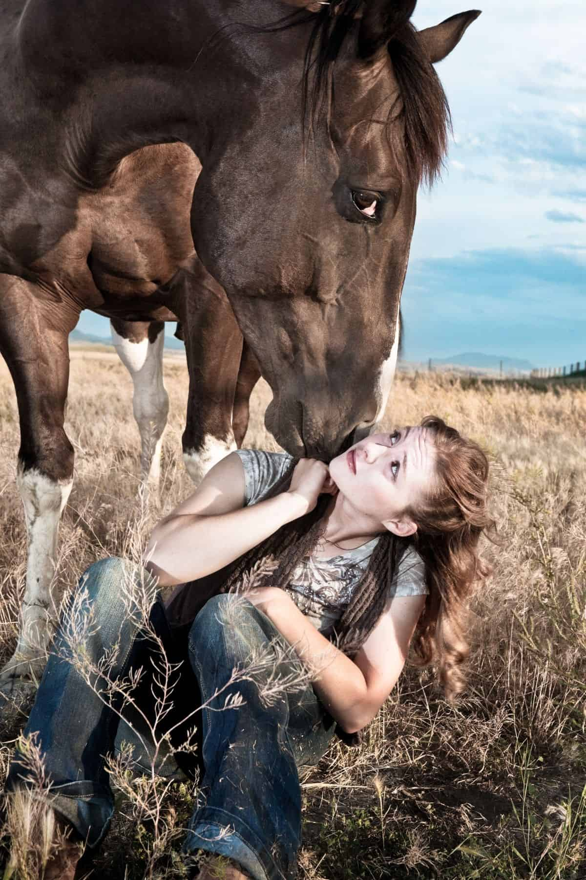 Brunette girl sitting on ground with horse above givin gkiss