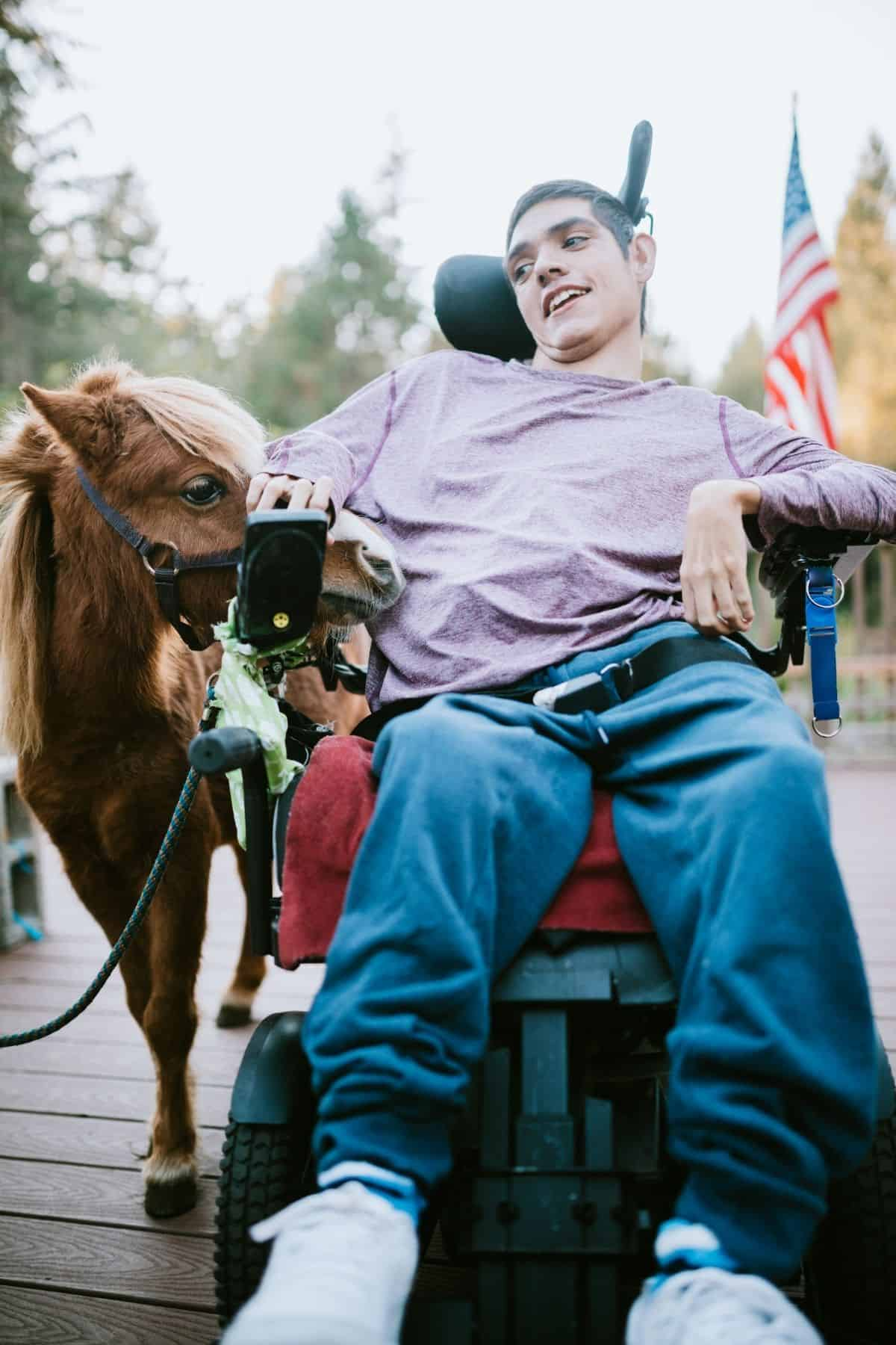 Man in purple shirt in wheelchair by horse