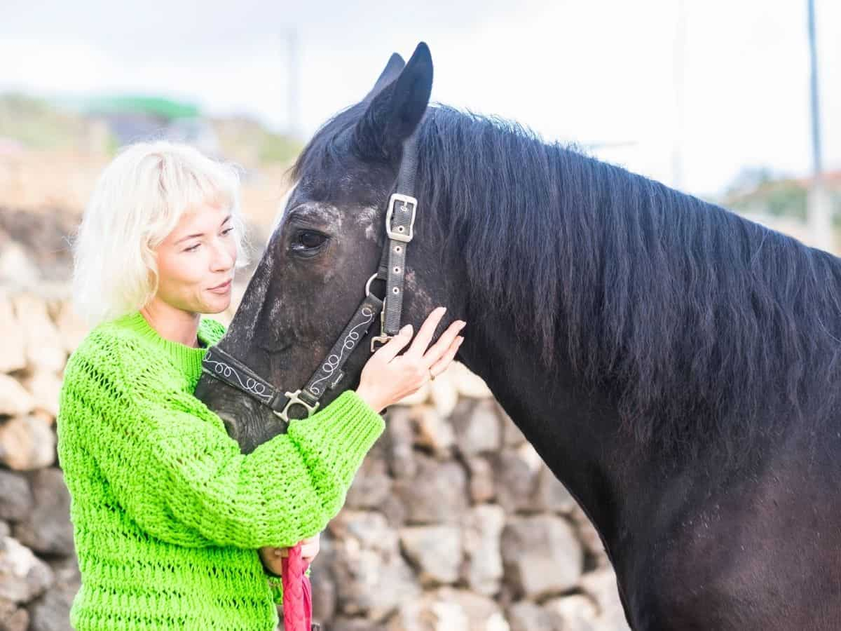 Woman in green holding black horse reigns