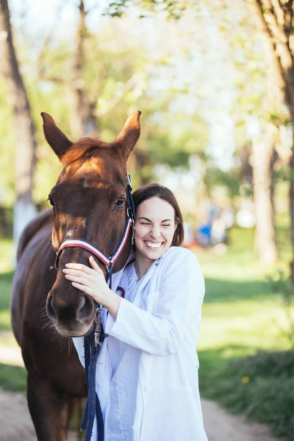 Woman smiling next to brown horse