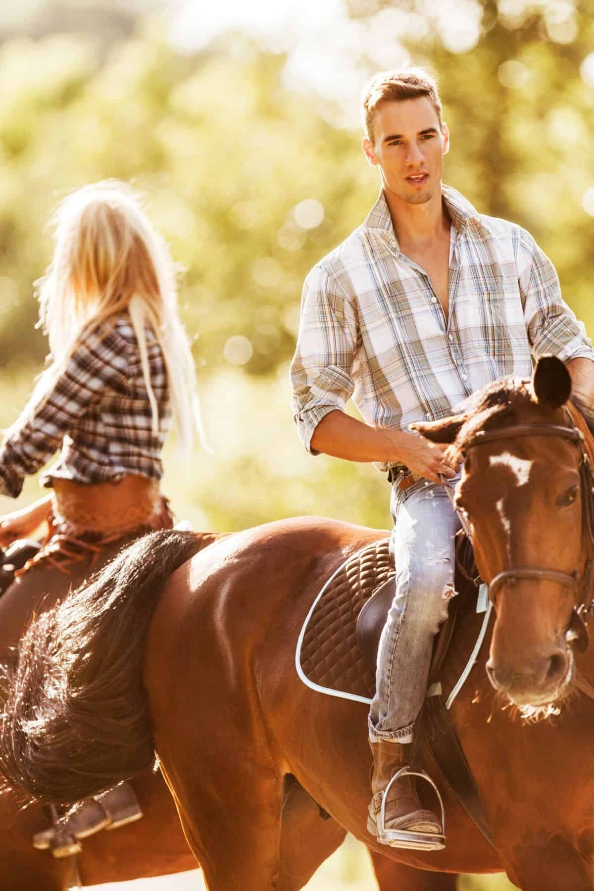 Couple on brown horses with glowing sunlight background