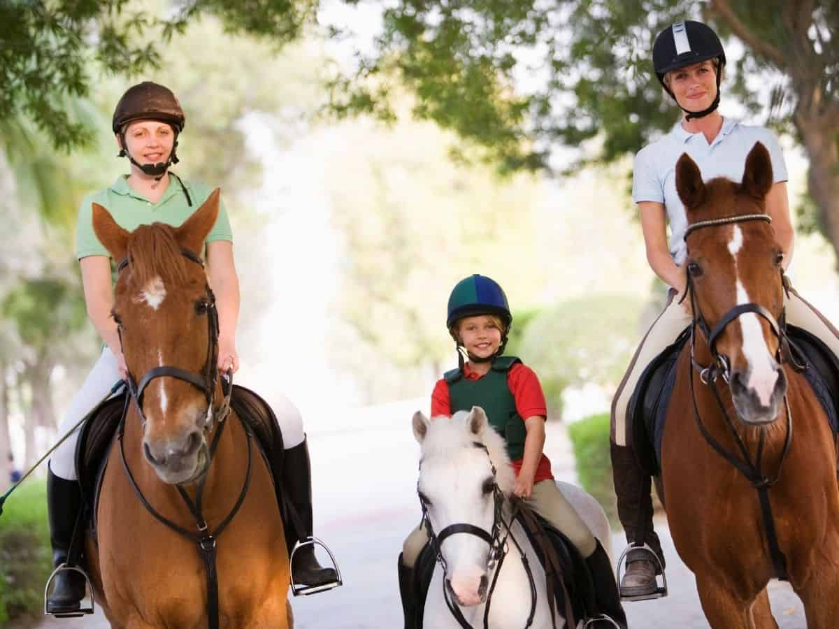 Family on three horses with white pony in middle