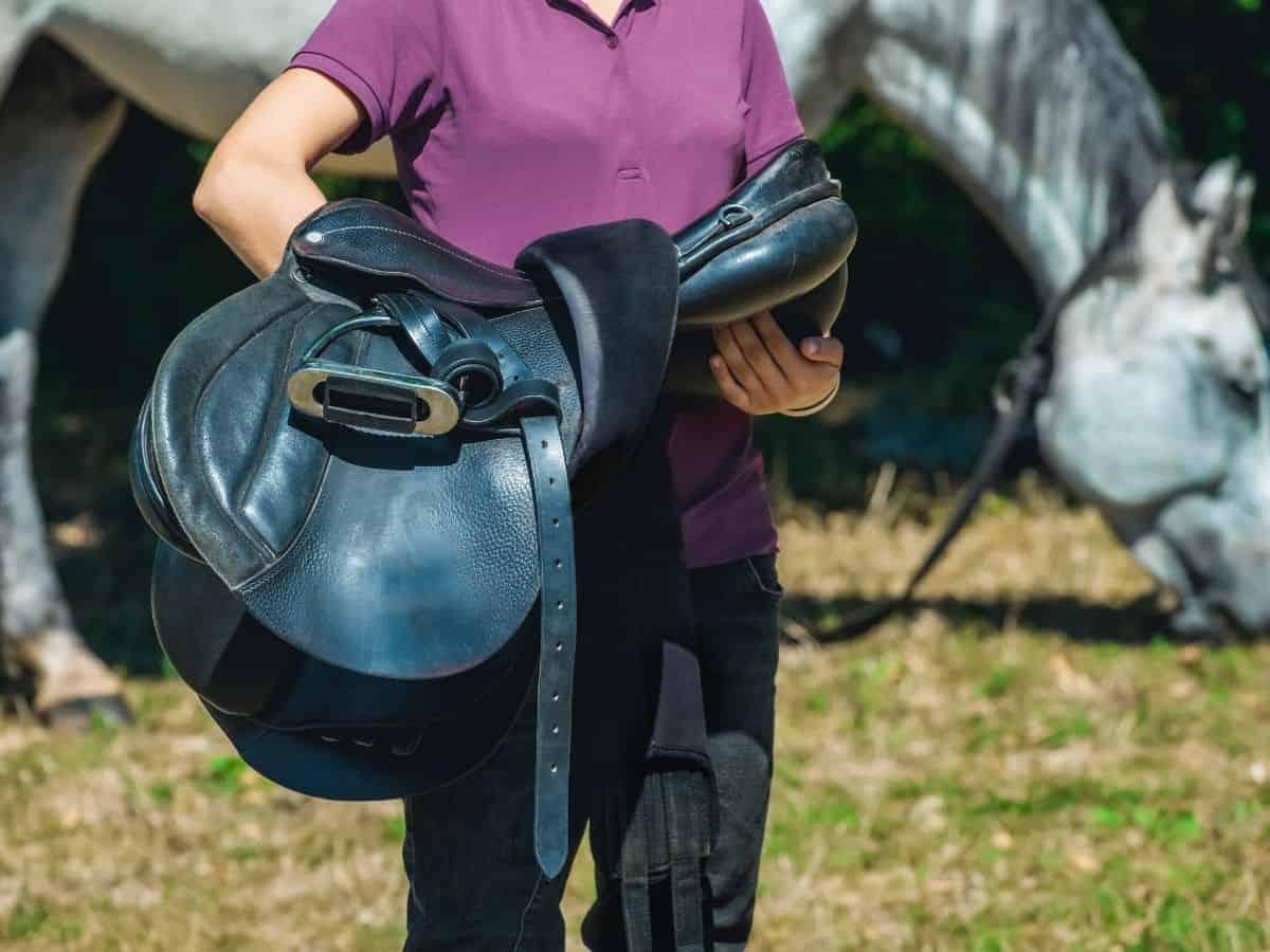 Woman in purple shirt carrying black saddle