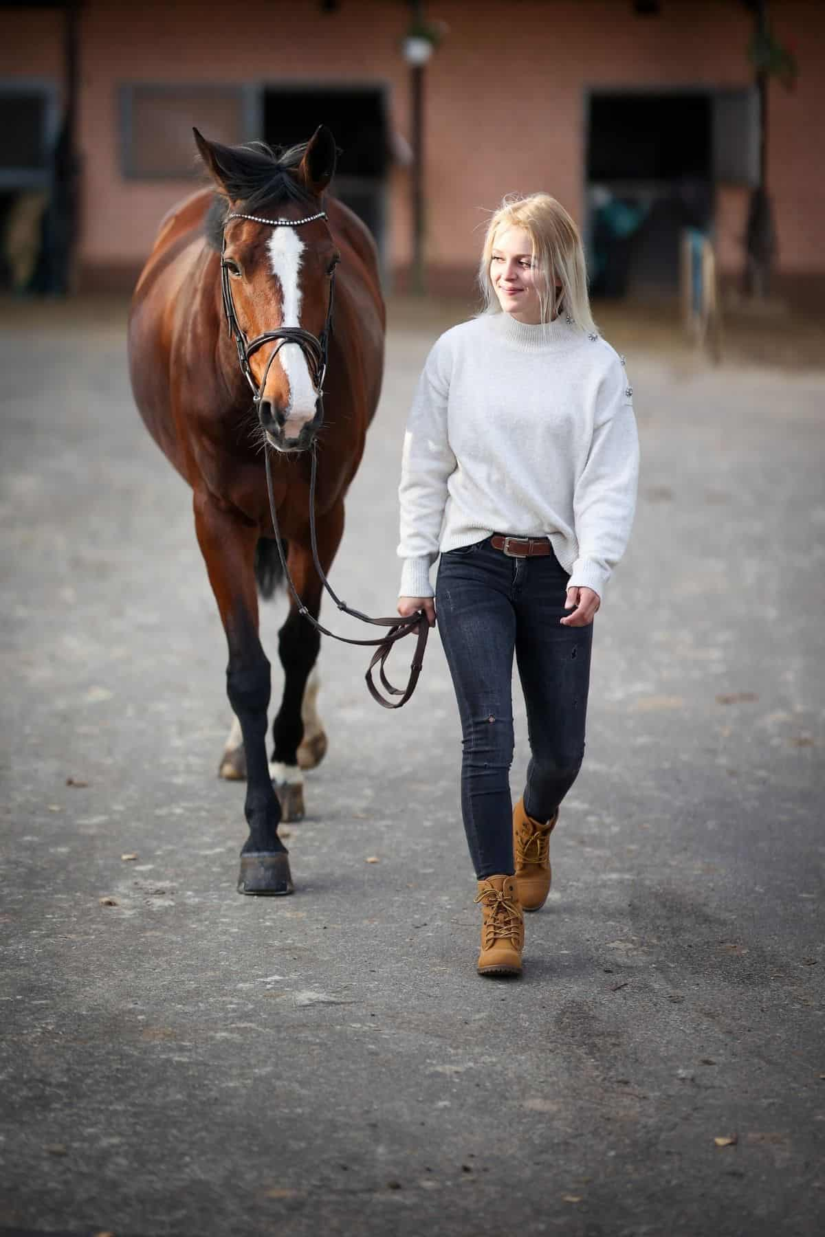 woman in white leading brown horse