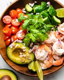A photo of poached shrimp salad with avocado cucumber tomatoes