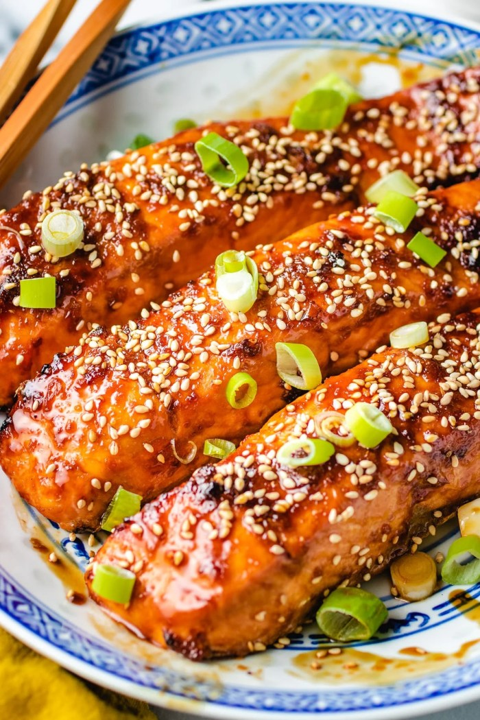 Photo shows garnishing the fish with sesame seeds and scallions