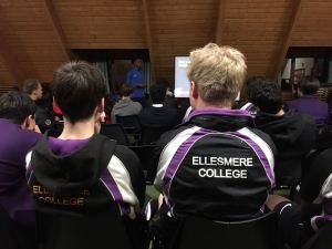 two teenage boys wearing school tracksuits listen intently to a presentation
