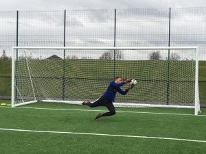a young goalkeeper in dark blue kit makes a brave dive to save the ball from going into the net