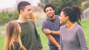 A group of young people smiling and talking in a park