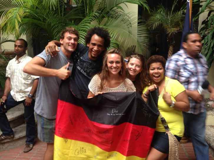Spanish and German language students cheering together with the German flag during the football world cup.
