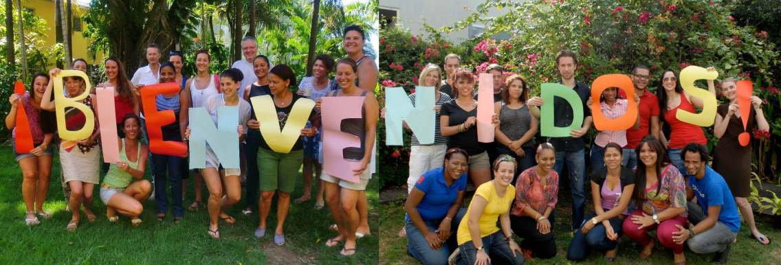 The two teams of IIC Santo Domingo and IIC Sosua hold the letters of the word Bienvenidos in their hand to greet new students for their Spanish language courses in the tropical garden of their school.
