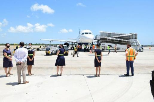 Flight attendants and personnel are standing on the tarmac in Punta Cana Airport to greet the first plane entering the Dominican Republic under covid19-terms after the reopening of the Dominican airports.