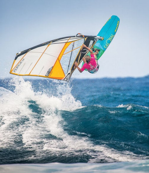 Windsurfer jumps and rides the waves, representing one of the disciplines of the Master of the Ocean watersports contest in Cabarete, Dominican Republic.