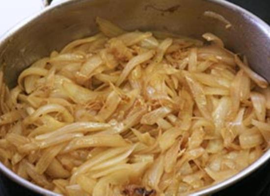 Карамелизируйте лук уменьшив пламя под сковородой до среднего уровня