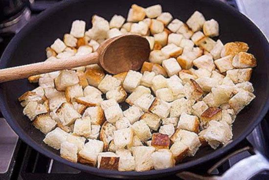 Разровняйте нарезанный кубиками хлеб по дну сковороды в один слой и жарьте
